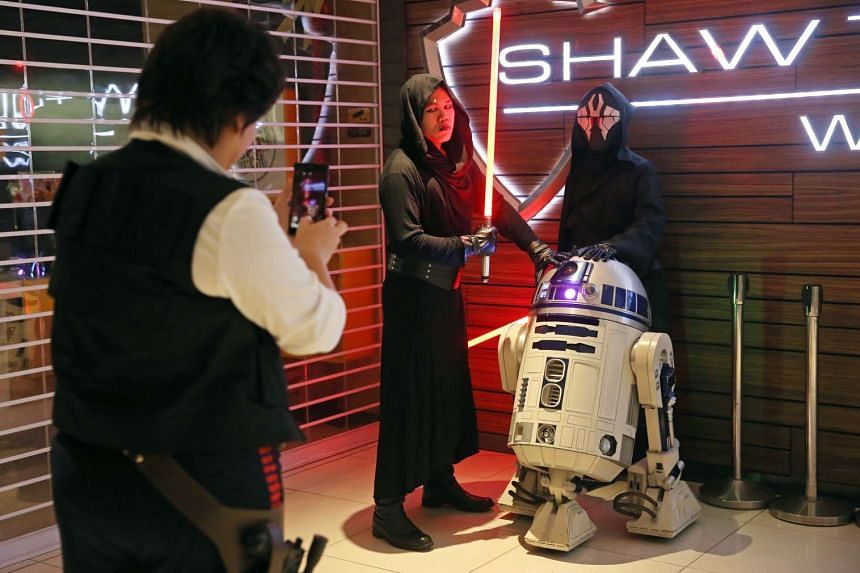 Fans dressed up in characters taking a photo with R2-D2 at the gala premiere of Star Wars: The Force Awakens on Dec 16, 2015.