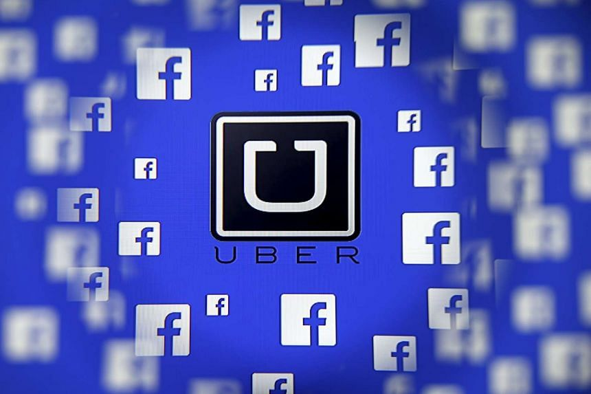 Logo of the Uber and Facebook are seen through magnifier on display in this photograph illustration.