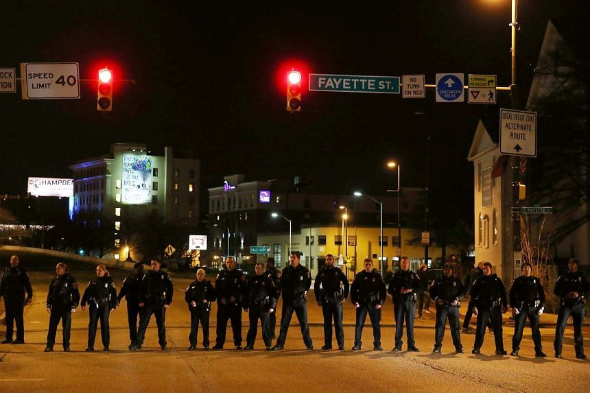 Police stand guard as protesters march through the streets, hours after a mistrial was declared in the trial of a Baltimore police officer.