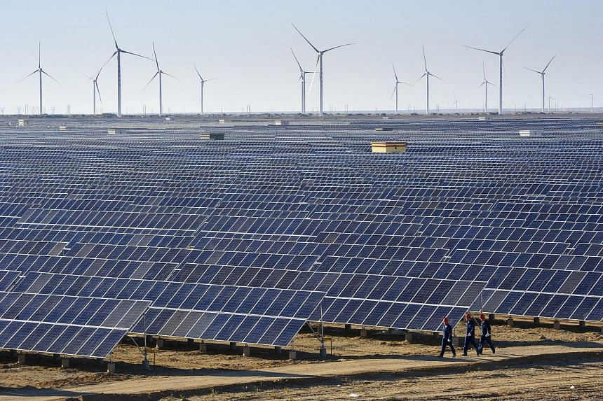 While wind and sunshine are free, wind turbines and solar panels, like these at a power plant in Xinjiang, China, are not. Fossil fuels are also needed to build these facilities and produce solar cells, says the writer.