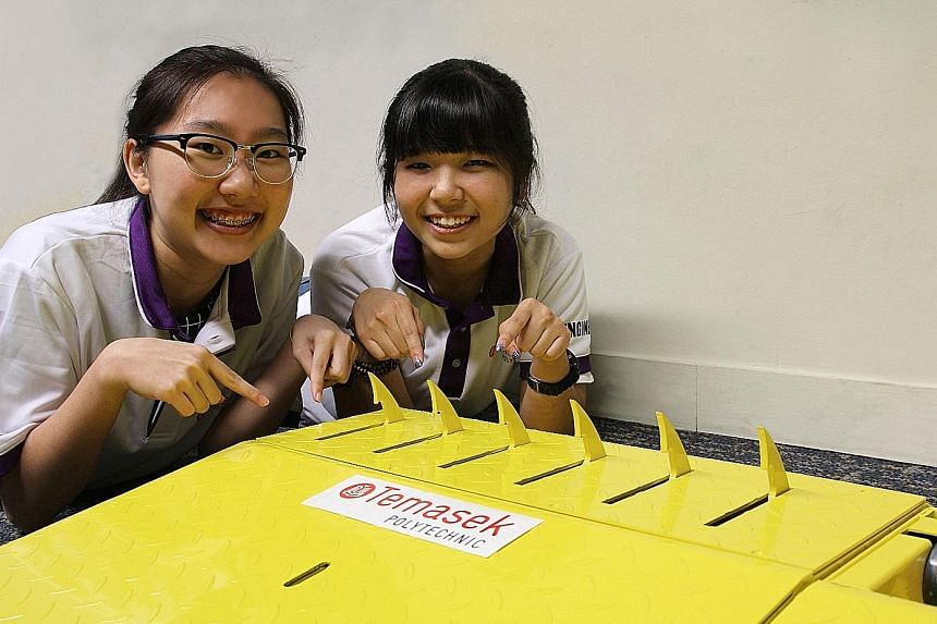 Temasek Polytechnic students Ho Ying Jie and Celeste Tan with the Speed Sensitive Spike Ramp. It can be installed onto any surface in five to 10 minutes. Weighing about 20kg, the ramp is portable.
