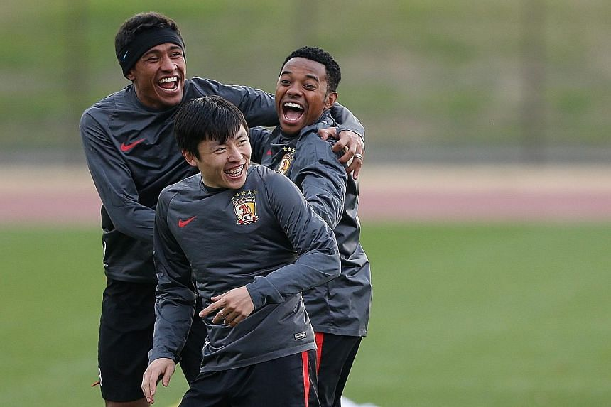 Guangzhou Evergrande's Brazilian connection Paulinho (left) and Robinho (right) laughing with Zheng Long during their training session in Yokohama ahead of their semi-final clash with Barcelona.