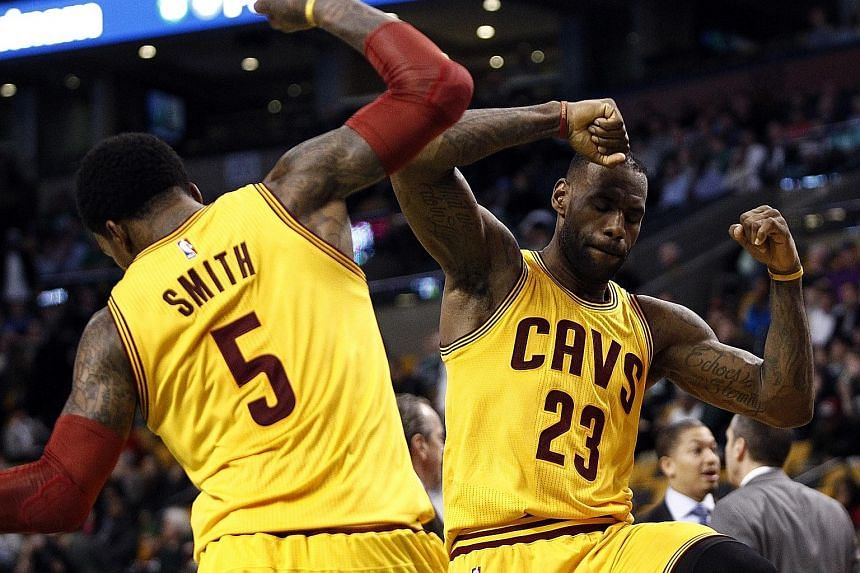 Cleveland Cavaliers forward LeBron James (right) and guard J.R. Smith celebrating against the Boston Celtics during the second half at TD Garden. The Cavs beat the Celtics 89-77.