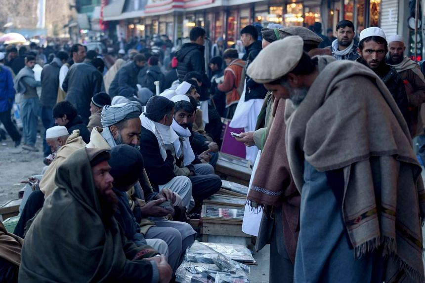 Afghan money changers wait for customers at a market in Kabul.