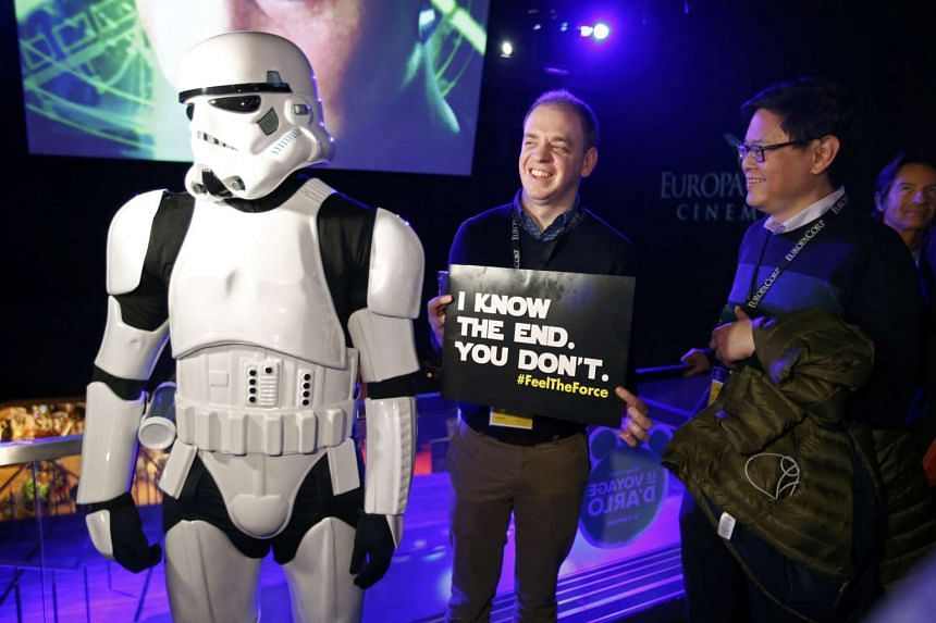 Two American Star Wars fans pose next to a Storm Trooper as they arrive at a cinema at Tremblay-en-France on Wednesday.