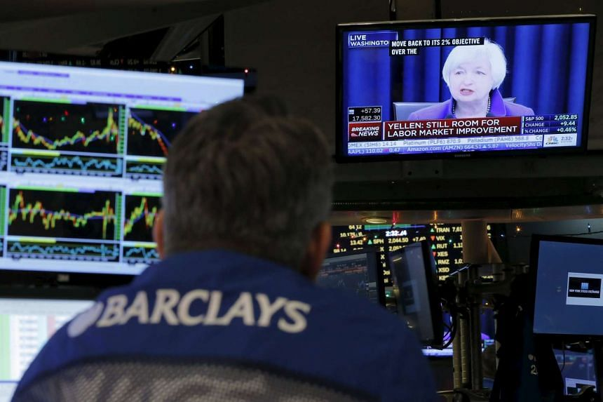 Traders at the New York Stock Exchange watching Fed chairman Janet Yellen speak on TV.