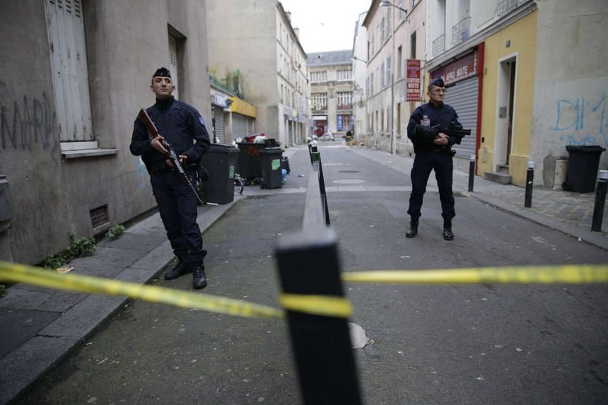 French riot police stand guard at the entrance of a cordened off area during a police raid on Nov 19, 2015.