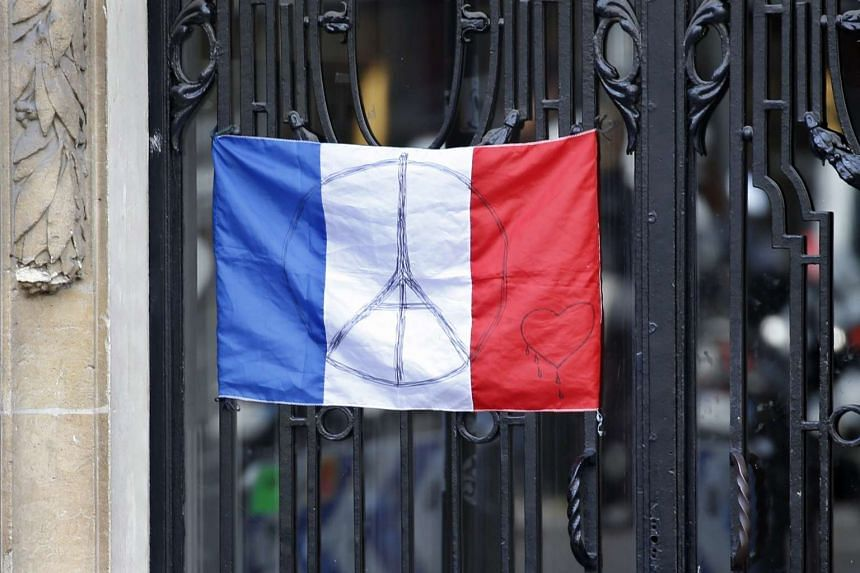 A French flag with the peace symbol is displayed at an apartment in Paris on Nov 26.