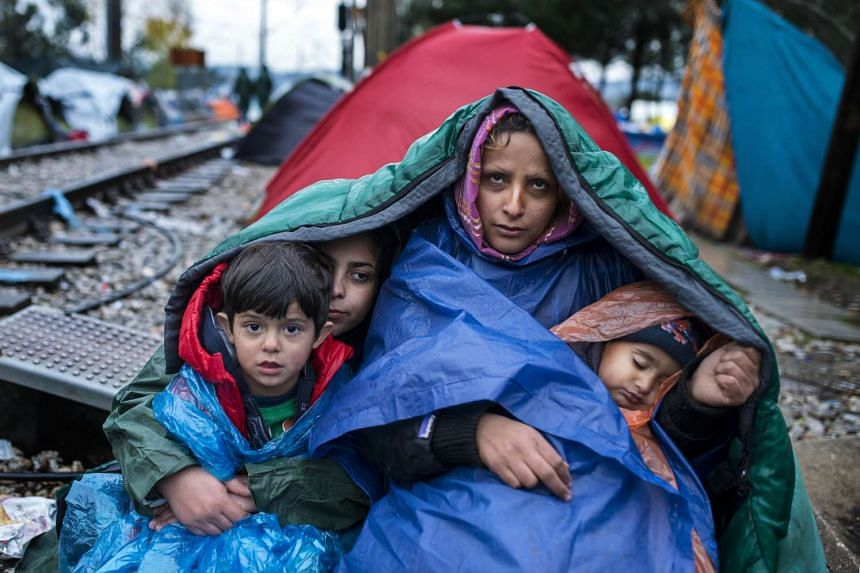 A woman and her children waiting to cross the Greece-Macedonia border in the rain on Nov 27.