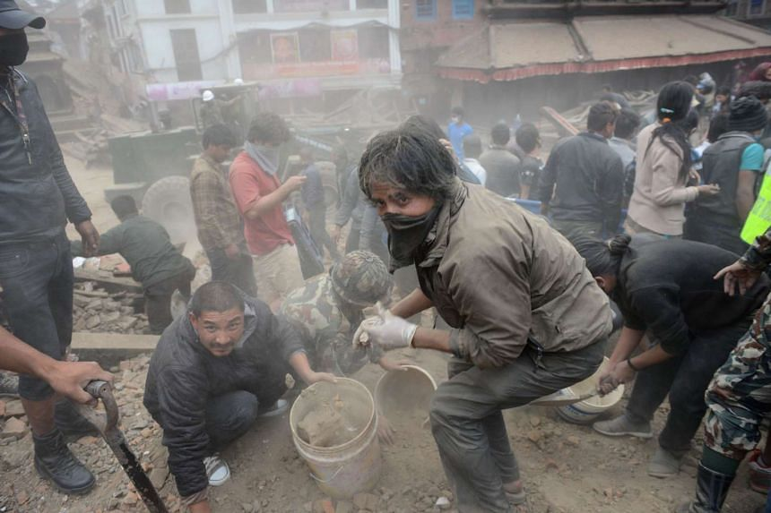 People clear rubble in Kathmandu's Durbar Square after the earthquake on April 25, 2015.