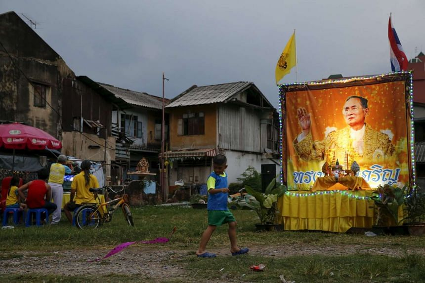 A boy runs next to a portrait of Thailand's King Bhumibol Adulyadej, placed in celebration of the King's 88th birthday, in Bangkok, Thailand, on Dec 5, 2015.