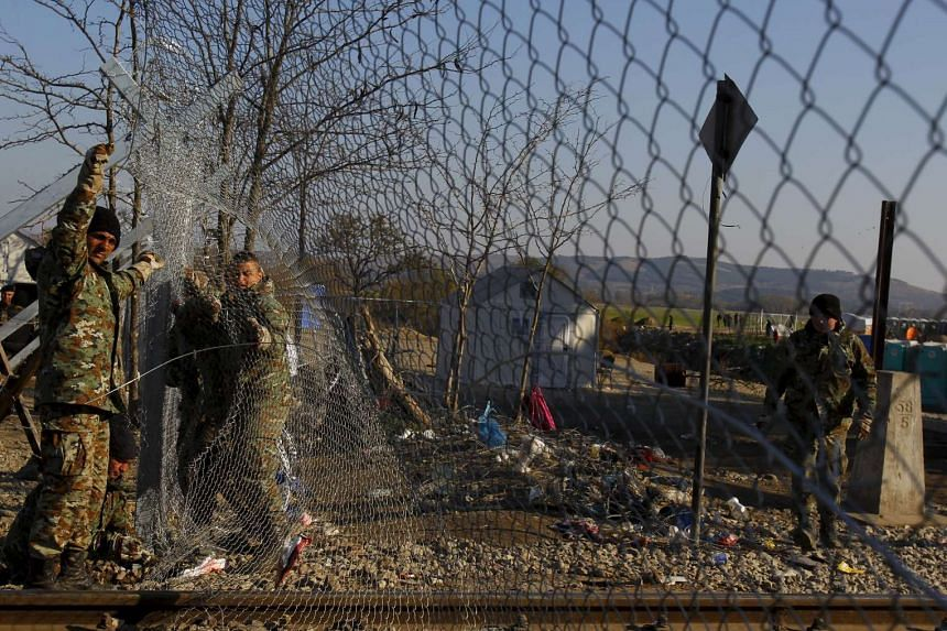 Soldiers put back a section of a barbed wire fence near on the Greek-Macedonian border.