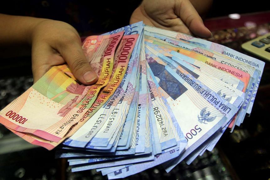 An Indonesian vendor holding Rupiah notes at a market in Jakarta on Dec 10.