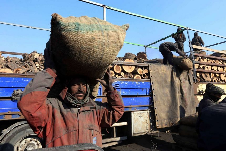 An Afghan boy sells coal to be used for fire, in Herat, Afghanistan.