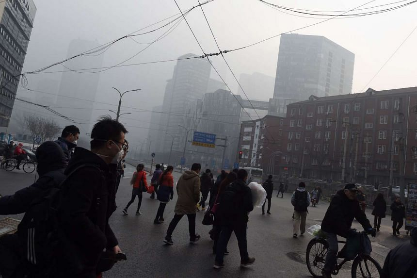 People cross a road on a polluted day in Beijing on Dec 14, 2015.