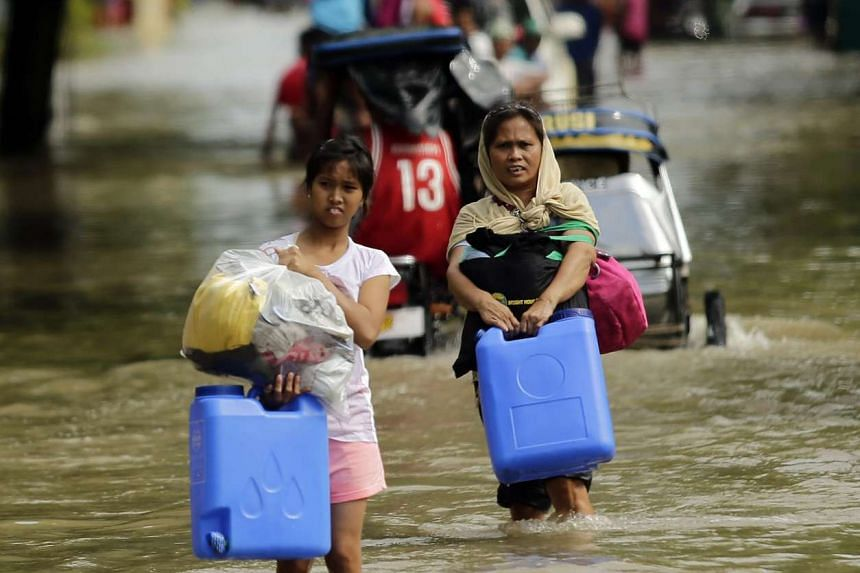 Filipino villages manoeuvre through flooded streets with their belongings.