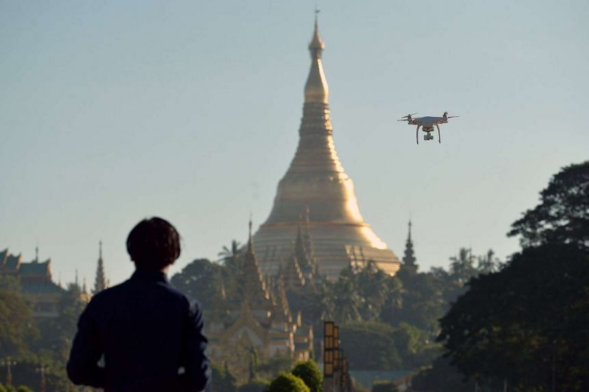 A drone enthusiast pilots his remote controlled aircraft at the people's park in front of the Shwedagon pagoda in Yangon.