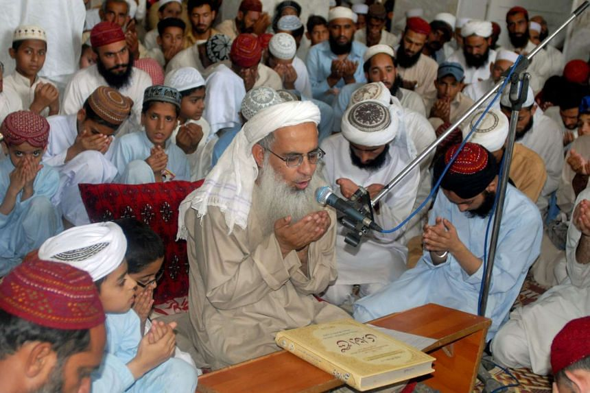 Red Mosque chief cleric Maulana Abdul Aziz (centre) prays, flanked by his followers.