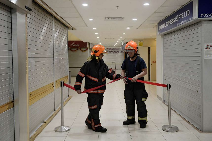 SCDF officers cordoning off an area on the second floor of Lucky Plaza.