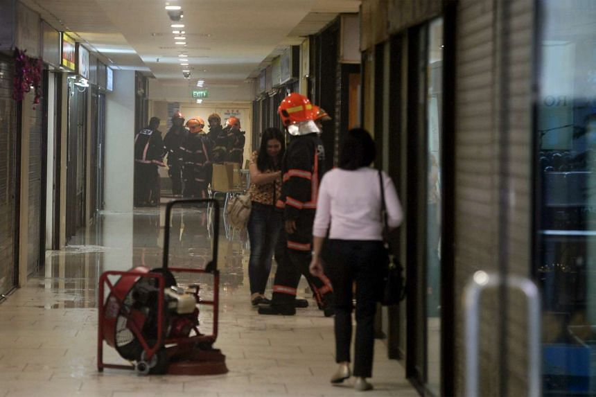 SCDF officers escorting people away from the second floor of Lucky Plaza.