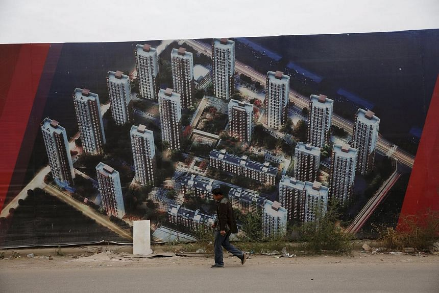 A man walking past a wall at a construction site for a new residential compound in Tianjin on Oct 18.
