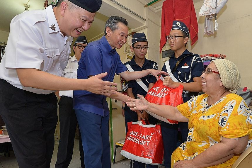"""Boys' Brigade president Ho Yew Kee (at left) and Share-A-Gift 2015 chairman Lui Chong Chee (centre) giving Madam Zainubi Abdul Majid two food hampers yesterday. She said she was """"very grateful to receive these gifts""""."""