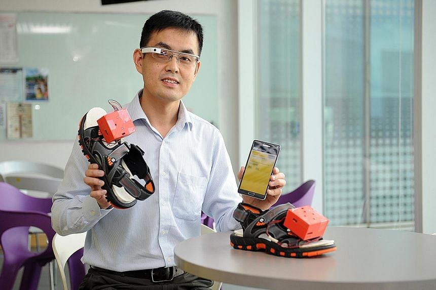 Dr Xu Qianli with the prototype of his wearable navigation assistance for the visually disabled. It comprises a Google Glass device, a mobile phone app and vibrating motors that can be embedded in a user's shoes.