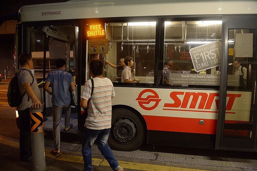 Commuters taking the free shuttle bus at Joo Koon station yesterday. A section of the East-West Line was disrupted for more than two hours in the evening.