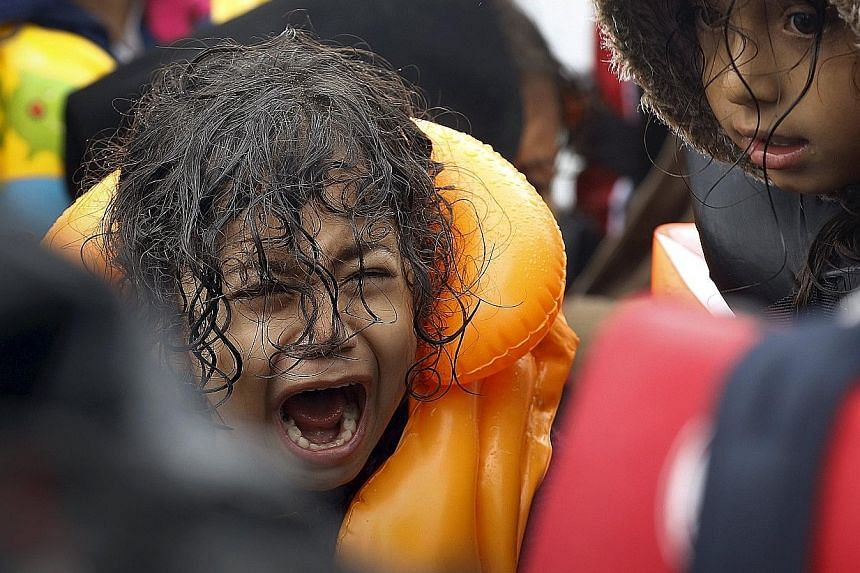 A Syrian refugee in distress after crossing part of the Aegean Sea from Turkey to the Greek island of Lesbos in an overcrowded dinghy in September.