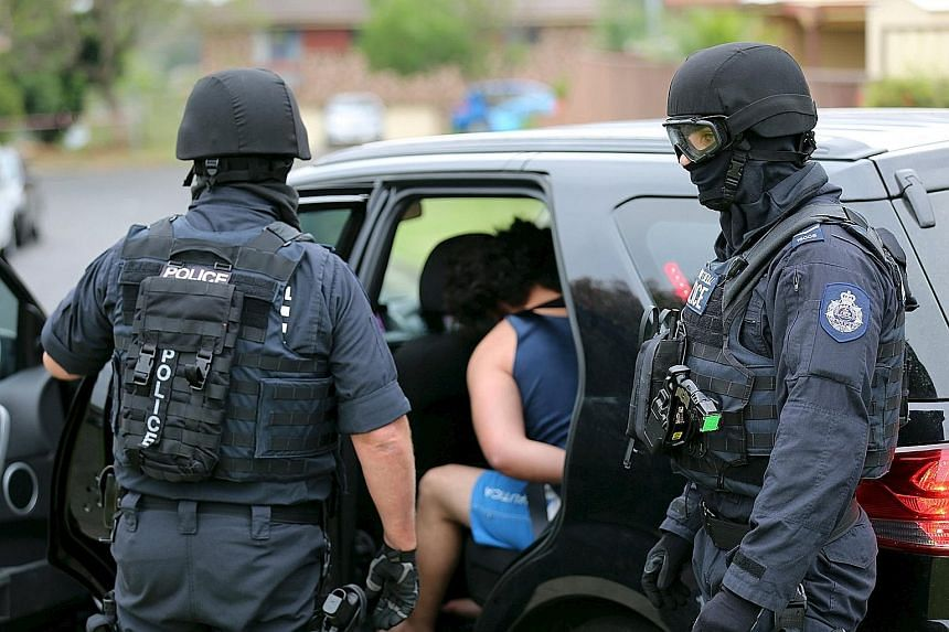 Heavily armed police detaining a man in Sydney on Dec 10. Australian police said they had charged a 20-year-old man and a 15-year-old boy with conspiracy to conduct an act of terrorism after they were arrested during the early-morning raids. In the p
