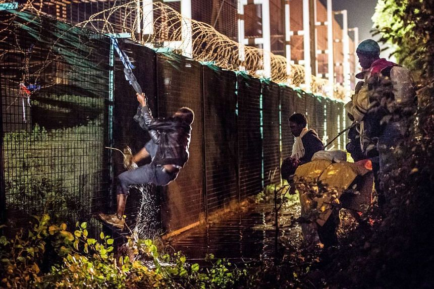 A migrant climbing the security fence of the Eurotunnel terminal in July 2015.