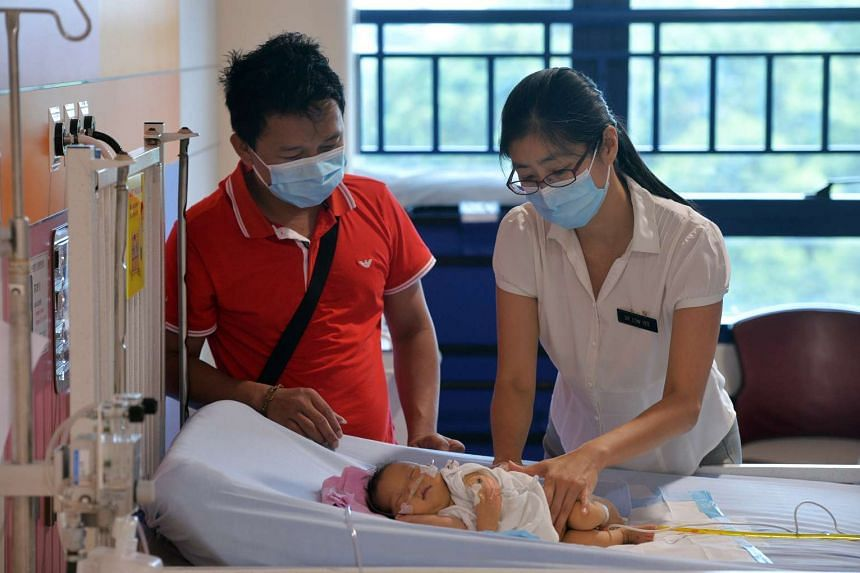 Prof Low Yee doing a routine check on Jeslyn as the infant's father, Mr Junaidi Lim, watches. The tumour, which measured 25cm, was removed after a seven-hour operation. Her condition has stabilised but she still needs oxygen for now and is under ob