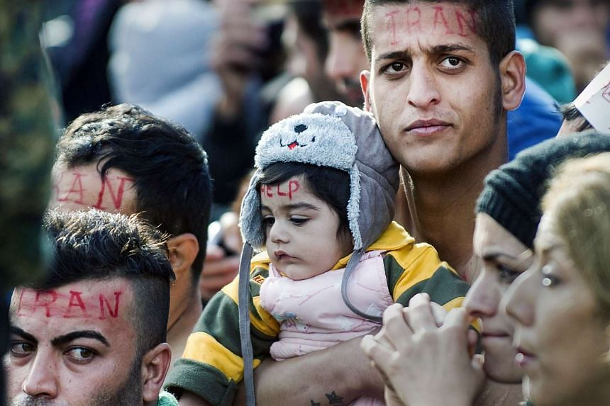 A man holding a baby while waiting to cross the Greek-Macedonian border on Nov 24.