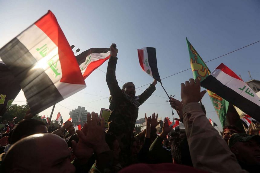 Iraqi protesters waving national flags during a demonstration in Baghdad's Tahrir Square on Dec 12, 2015, to demand the withdrawal of Turkish forces from Iraq.