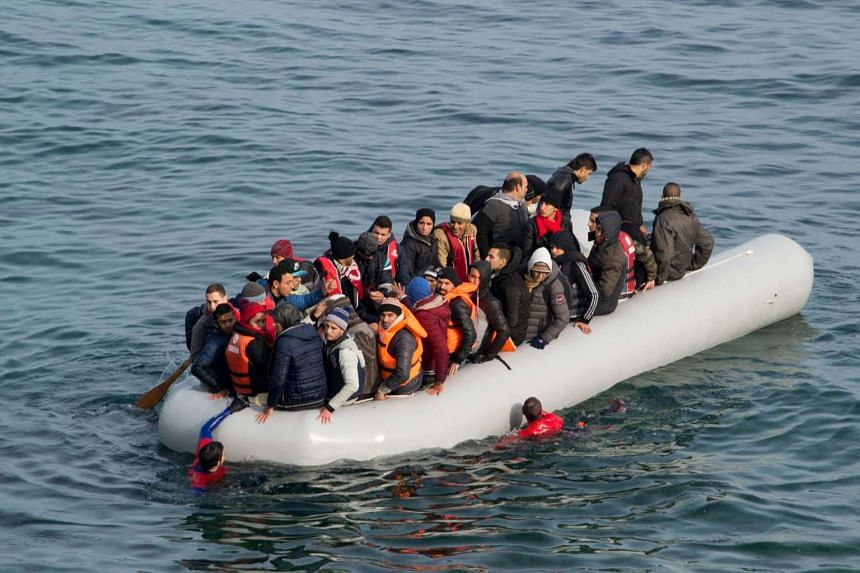 Refugees and migrants arrive in an overloaded rubber dinghy after crossing the Aegean Sea.
