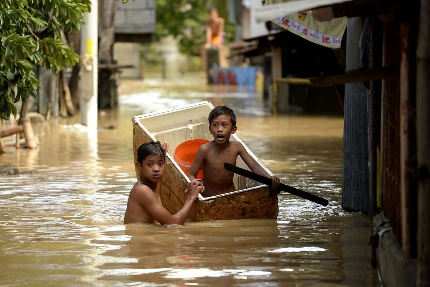 Children using a refrigerator as a boat to cross a flooded alley in Candaba, Pampanga, north of Manila on Dec 18, 2015.