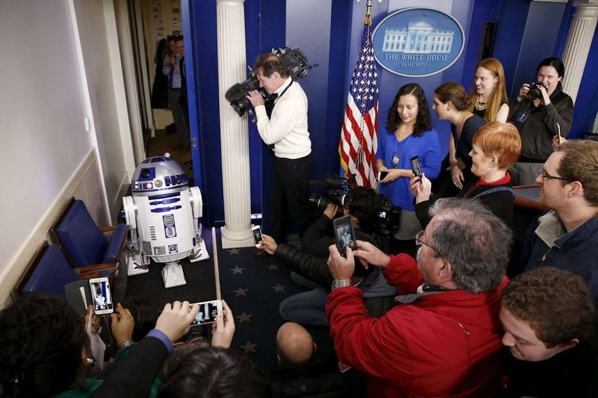 Journalists surrounding Star Wars character R2-D2, who was brought into the White House press briefing room after Mr Obama finished his end-of-year news conference on Dec 18.