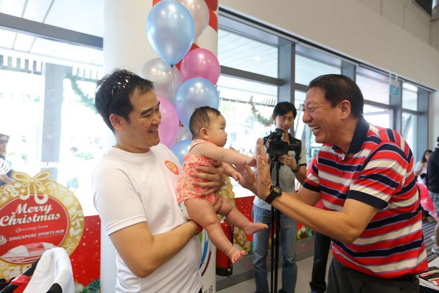DPM Teo (right) meeting an SG50 baby at the inaugural National Play Day carnival on Dec 19, 2015.