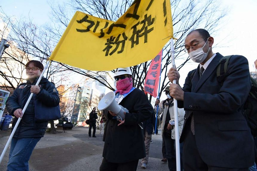 "Members of ""losers with women"", march as they shout anti-Christmas slogans at Shibuya shopping district in Tokyo."