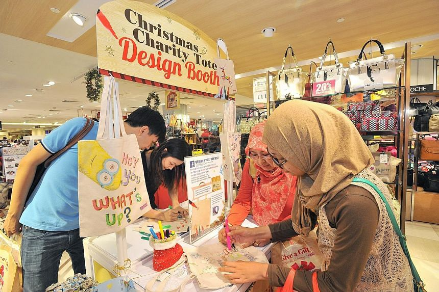 (From left) Salesman Vernard Ong, 30, his girlfriend, accountant Chrys Ng, 26, housewife Imas Nur Tjahyawati, 48, and student Ulfy Fitryani, 18, designing totes they bought at BHG at Bugis Junction yesterday. As part of BHG's Christmas Charity Tote i