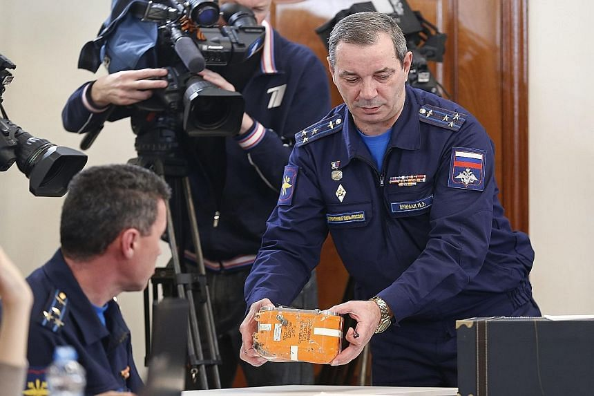 Aviation Accidents Investigation Commission head Nikolay Primak holding the black box during a live broadcast of its unsealing in Moscow yesterday.