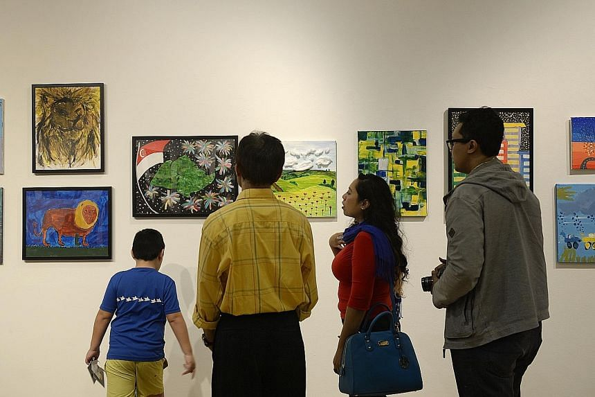 Visitors admiring paintings at Gifts, an exhibition by students from special-needs school Rainbow Centre, which opened at the Ion Art Gallery in Orchard yesterday. More than 100 artworks by over 40 students aged seven to 18 are on show from 10am to 9