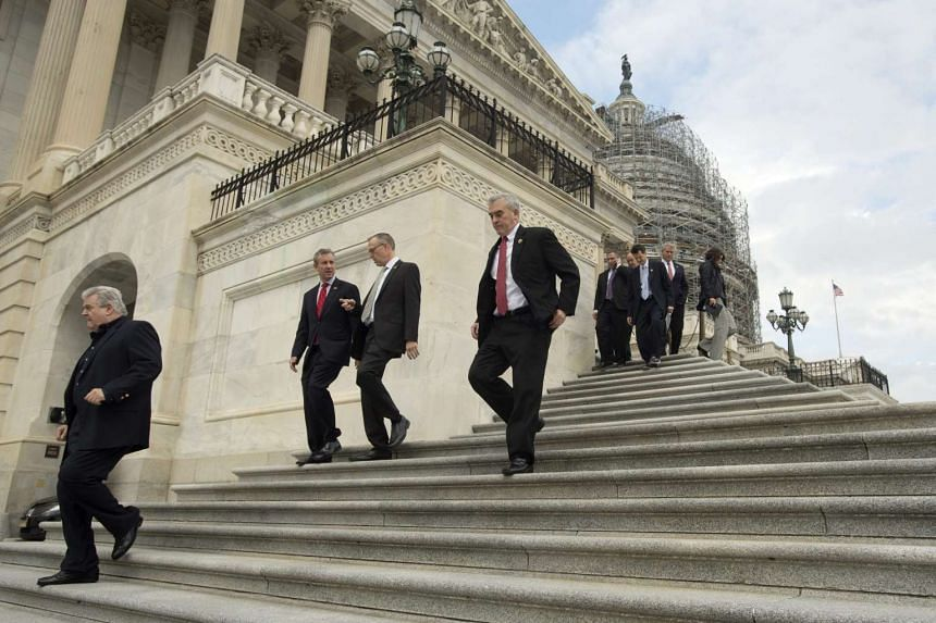 Members of Congress and aides exit the US House of Representatives.