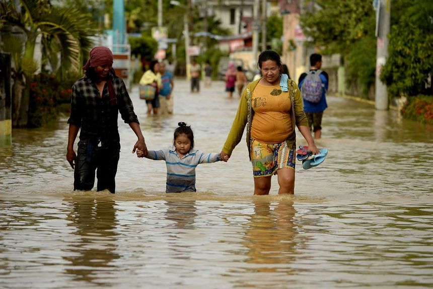 Residents crossing a flooded street to evacuate to a higher ground in Candaba, Pampanga, north of Manila on Dec 18, 2015.