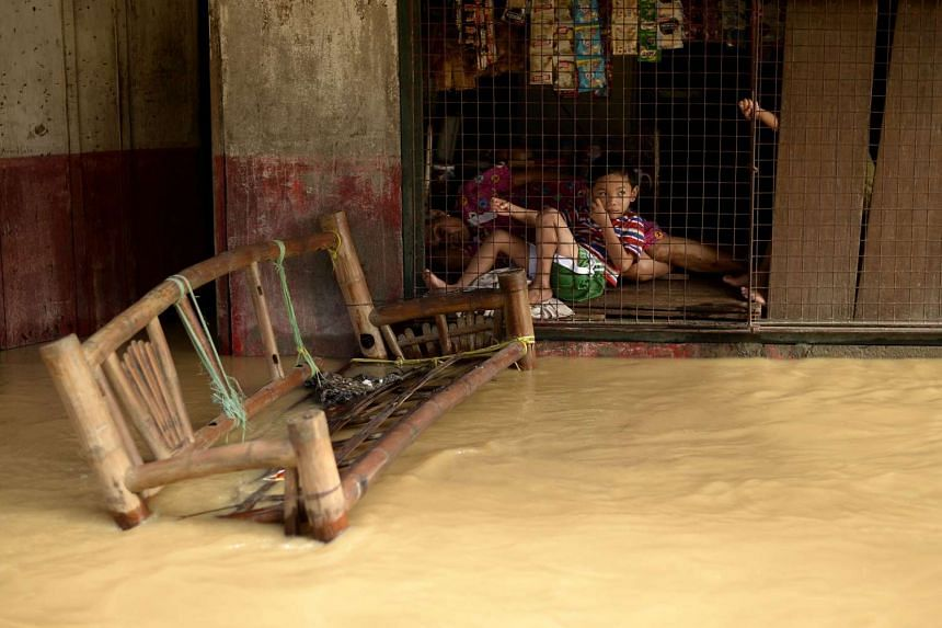 Children resting at the window of their flooded house in Candaba, Pampanga, north of Manila on Dec 18, 2015.
