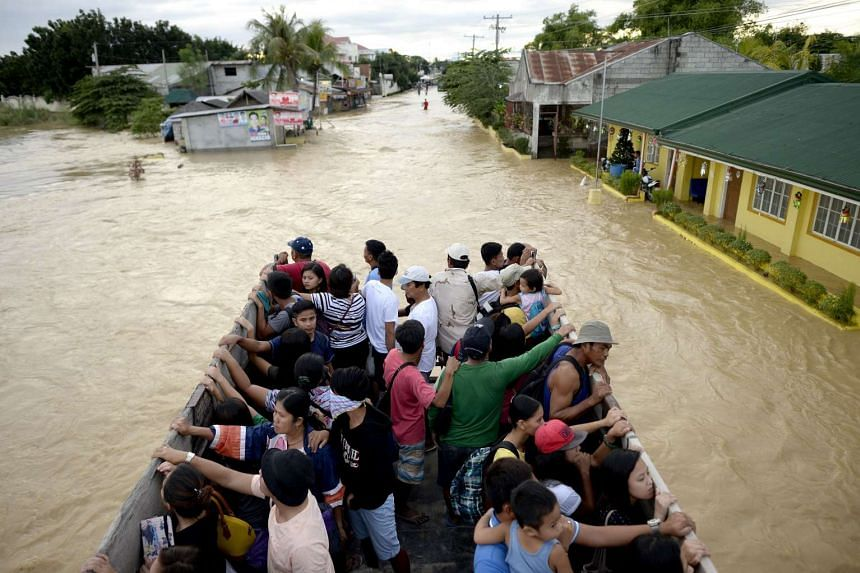 Residents riding on a truck over floodwaters to evacuate to higher ground in Candaba, Pampanga, north of Manila on Dec 18, 2015.