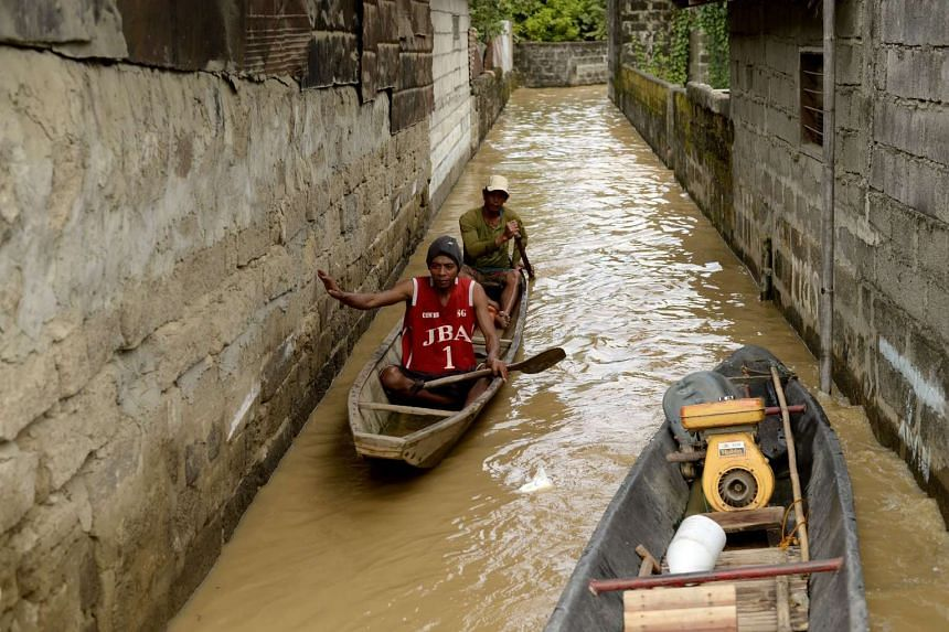 Residents using wooden boats to cross a flooded alley in Candaba, Pampanga, north of Manila on Dec18, 2015.