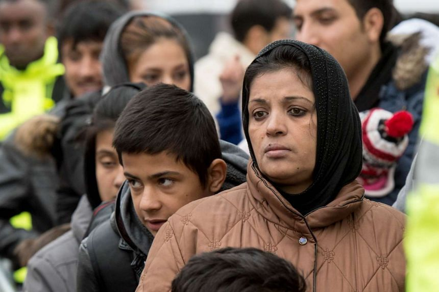 Asylum seekers wait to register after arriving in Giessen, western Germany.