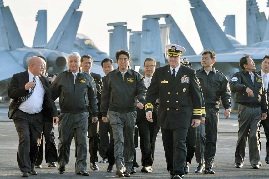 Japan's PM Shinzo Abe (centre), Deputy Prime Minister Taro Aso (far right) and Defence Minister Gen Nakatani (second from left) with Captain Chris Bolt of the USS Ronald Reagan on a visit to the US aircraft carrier in Sagami Bay in October.