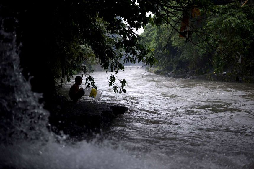 A boy looks at a swollen creek under a flyover in Manila, after heavy rains hit the Philippines, on Dec 19, 2015.